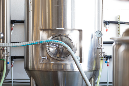 fermenting: EUGENE, OR - NOVEMBER 4, 2015: Stainless steel commercial beer fermenter at the startup craft brewery Mancave Brewing.