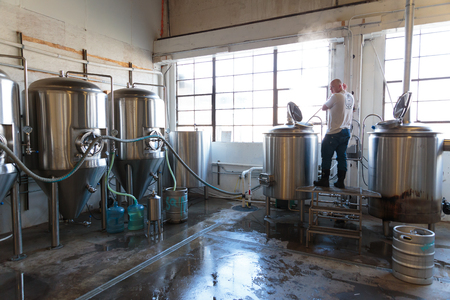 ipa: EUGENE, OR - NOVEMBER 4, 2015: Commercial brewery owner Brandon Woodruff mashing Exalted IPA at the startup craft brewery Mancave Brewing.