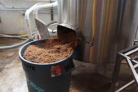 eugene: EUGENE, OR - NOVEMBER 4, 2015: Used mash is emptied from the mashing machine into a large bucket for recycling at the startup craft brewery Mancave Brewing. Editorial