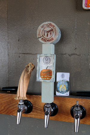 taphouse: EUGENE, OR - NOVEMBER 4, 2015: Custom tap handle at the startup craft brewery Mancave Brewing.