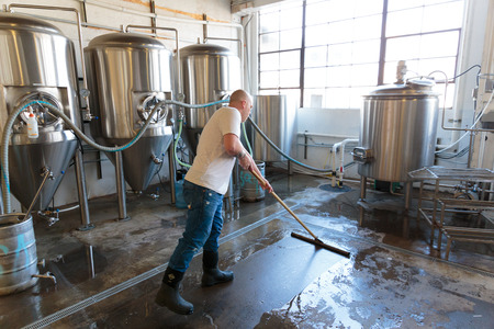 brewery: EUGENE, OR - NOVEMBER 4, 2015: Brewery owner Brandon Woodruff cleaning the floor at the startup craft brewery Mancave Brewing.