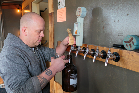 exalted: EUGENE, OR - NOVEMBER 4, 2015: Bartender and brewery co-owner Brandon Woodruff pouring Exalted IPA on tap at the startup craft brewery Mancave Brewing. Editorial
