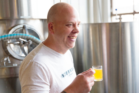 EUGENE, OR - NOVEMBER 4, 2015: Head brewmaster Brandon Woodruff sampling beer from a fermenter at the startup craft brewery Mancave Brewing.