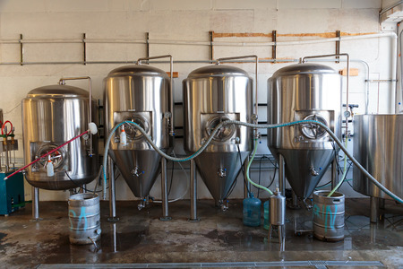 brewery: EUGENE, OR - NOVEMBER 4, 2015: Stainless steel commercial beer fermenter at the startup craft brewery Mancave Brewing.