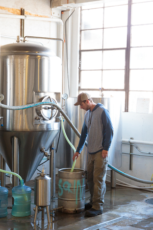 brewery: EUGENE, OR - NOVEMBER 4, 2015: Brewery owner Wes Gunderson brewing an IPA at the startup craft brewery Mancave Brewing.