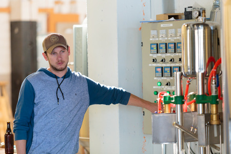 celcius: EUGENE, OR - NOVEMBER 4, 2015: Brewery co-owner Wes Gunderson controlling the temperature of a mashing machine at the startup craft brewery Mancave Brewing. Editorial
