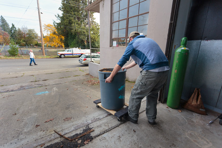 loading dock: EUGENE, OR - NOVEMBER 4, 2015: Brewery co-owner Wes Gunderson rides the mash bucket dolly down the loading dock at the startup craft brewery Mancave Brewing.