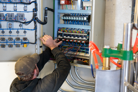 celcius: EUGENE, OR - NOVEMBER 4, 2015: Electrician working on an electrical output control panel at the startup craft brewery Mancave Brewing.