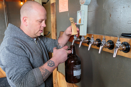 taphouse: EUGENE, OR - NOVEMBER 4, 2015: Bartender and brewery co-owner Brandon Woodruff pouring Exalted IPA on tap at the startup craft brewery Mancave Brewing. Editorial