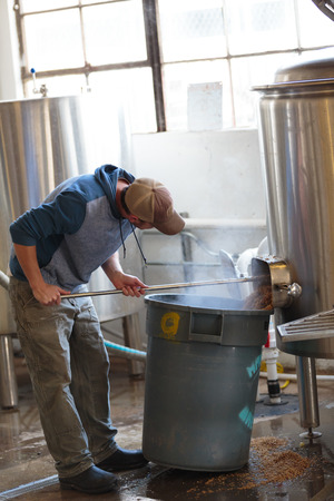 ipa: EUGENE, OR - NOVEMBER 4, 2015: Brewery owner Wes Gunderson brewing an IPA at the startup craft brewery Mancave Brewing.