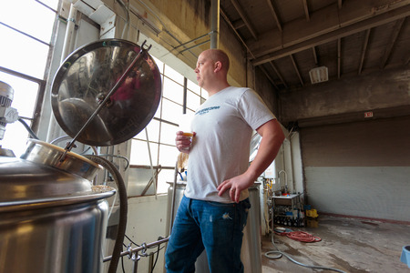 ipa: EUGENE, OR - NOVEMBER 4, 2015: Head brewmaster Brandon Woodruff brewing an IPA at the startup craft brewery Mancave Brewing.