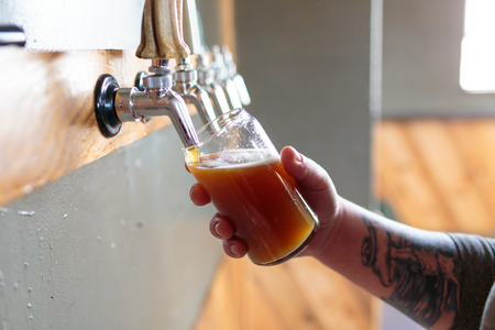 EUGENE, OR - NOVEMBER 4, 2015: Bartender and brewery co-owner Brandon Woodruff pouring Exalted IPA on tap at the startup craft brewery Mancave Brewing. Redactioneel