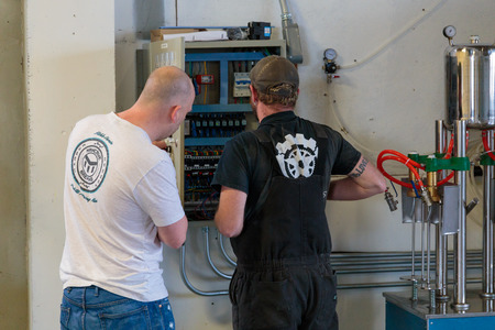 celcius: EUGENE, OR - NOVEMBER 4, 2015: Brewery co-owner Brandon Woodruff works with an electrician to resolve a technical issue with an electrical control panel at the startup craft brewery Mancave Brewing.