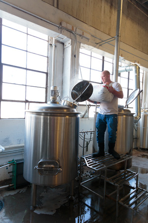 brewery: EUGENE, OR - NOVEMBER 4, 2015: Commercial brewery owner Brandon Woodruff mashing Exalted IPA at the startup craft brewery Mancave Brewing.
