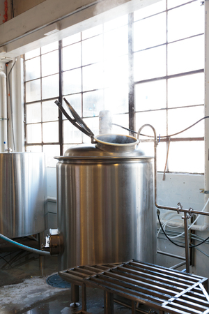 eugene: EUGENE, OR - NOVEMBER 4, 2015: Stainless steel commercial beer fermenter at the startup craft brewery Mancave Brewing.