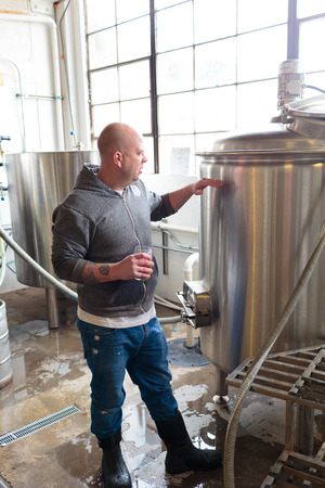 ipa: EUGENE, OR - NOVEMBER 4, 2015: Head brewmaster Brandon Woodruff commercially brewing an IPA at the startup craft brewery Mancave Brewing. Editorial