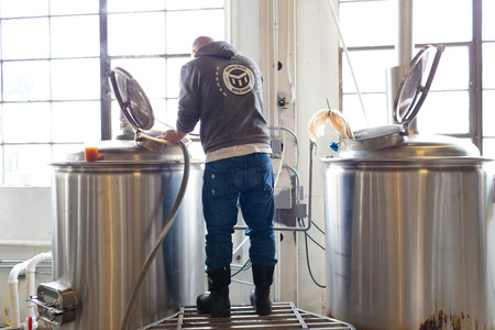 eugene: EUGENE, OR - NOVEMBER 4, 2015: Head brewmaster Brandon Woodruff commercially brewing an IPA at the startup craft brewery Mancave Brewing. Editorial