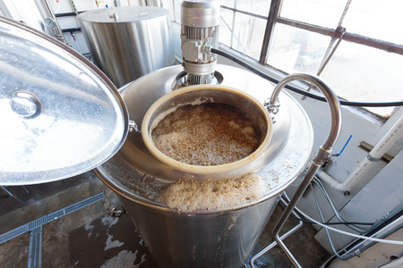 brewery: EUGENE, OR - NOVEMBER 4, 2015: Boiling all grain mash to create wort in the commercial brewing process at the startup craft brewery Mancave Brewing.