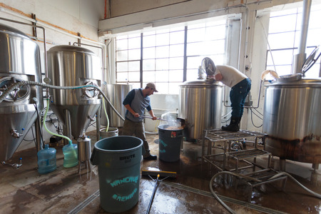brewery: EUGENE, OR - NOVEMBER 4, 2015: Brewery co-owners Brandon Woodruff and Wes Gunderson work together to create the award-winning Exalted IPA at the startup craft brewery Mancave Brewing. Editorial