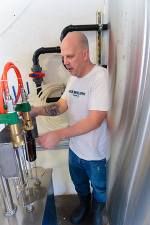 EUGENE, OR - NOVEMBER 4, 2015: Brandon Woodruff operating a beer bottling maching at the startup craft brewery Mancave Brewing.