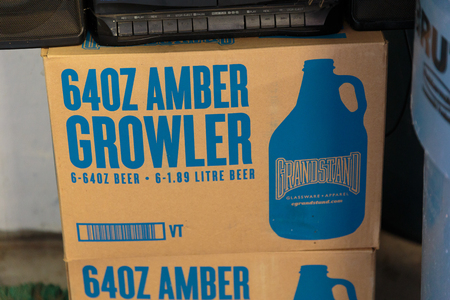 eugene: EUGENE, OR - NOVEMBER 4, 2015: 64oz amber beer growlers in a box at the startup craft brewery Mancave Brewing.