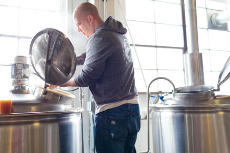 commercially: EUGENE, OR - NOVEMBER 4, 2015: Head brewmaster Brandon Woodruff commercially brewing an IPA at the startup craft brewery Mancave Brewing. Editorial