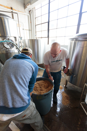 ipa: EUGENE, OR - NOVEMBER 4, 2015: Brewery co-owners Brandon Woodruff and Wes Gunderson work together to create the award-winning Exalted IPA at the startup craft brewery Mancave Brewing. Editorial
