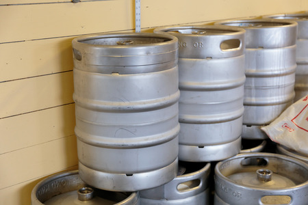 kegs: EUGENE, OR - NOVEMBER 4, 2015: Stainless steel beer kegs stacked together at the startup craft brewery Mancave Brewing.