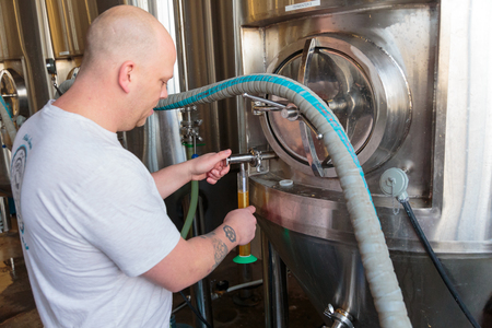 EUGENE, OR - NOVEMBER 4, 2015: Head brewmaster Brandon Woodruff sampling beer from a fermenter at the startup craft brewery Mancave Brewing. Stok Fotoğraf - 47700061