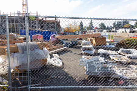 site construction: EUGENE, OR - NOVEMBER 4, 2015: Fenced off construction site with ample building materials and supplies.