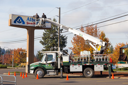 EUGENE, OR - NOVEMBER 4, 2015: Two workers installing a new sign at an Albertsons location at Oakway Center. Editorial