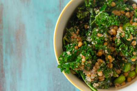 Superfood salad with raw kale, quinoa, blueberries, and barley is perfect for the paleo diet for weight loss. Stock Photo