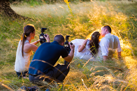 photographers: EUGENE, OR - AUGUST 2, 2014: Videographers filiming a bride and groom in a field of tall grass after a wedding ceremony.