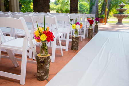 White chairs and rows of seating create a nice venue for the bride to walk down the aisle at this wedding ceremony.