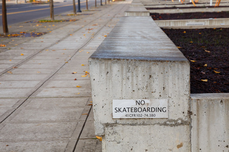 enforce: No skateboarding sign fixed to a concrete ledge to enforce city ordinance for public buildings.