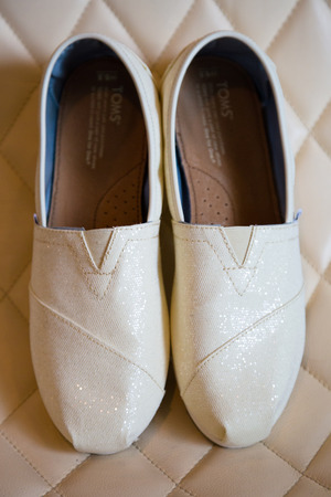 PORTLAND, OR - AUGUST 30, 2014: White leather Toms brand shoes on a patterned chair for the bride to wear during her wedding ceremony.