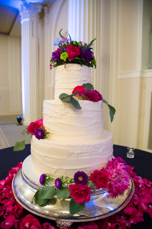 standing reception: White wedding cake standing tall at a reception before guests get to enjoy dessert. Stock Photo