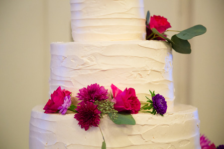 c�r�monie mariage: White wedding cake standing tall at a reception before guests get to enjoy dessert. Banque d'images