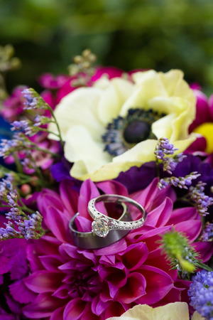 Flowers make the backdrop for the bride and groom wedding rings at a ceremony in Oregon. Imagens