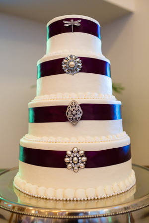 cake tier: Tall white wedding cake wrapped in purple ribbon with brooches attached to each tier of the dessert.