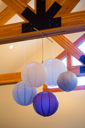 rafters: Chinese of Japanese paper lanterns hang from wood rafters at a wedding reception for decor.