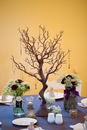 Wedding reception decor includes this centerpiec made out of an interesting tree and flowers in jars.