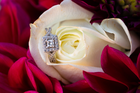 The wedding ring of the bride on a white rose flower at a wedding ceremony.