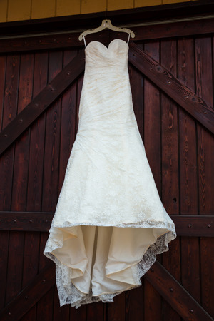 large doors: white wedding dress hanging on large maroon stained doors at a winery