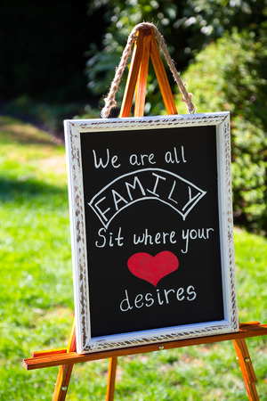 desires: Wedding sign for seating arrangements says we are all family sit where your heart desires.