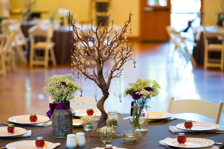 floral decoration: Wedding reception decor includes this centerpiec made out of an interesting tree and flowers in jars.