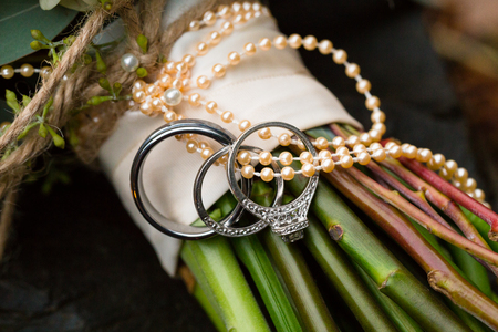 vows: Wedding rings for the bride and groom photographed with a closeup lens on the bouquet of flowers to be carried by the bride.