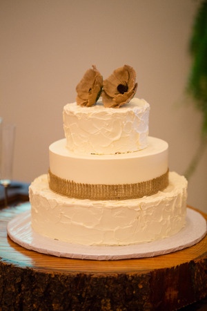 boda pastel: Wood round holding a wedding cake for the bride and groom to cut at their reception.