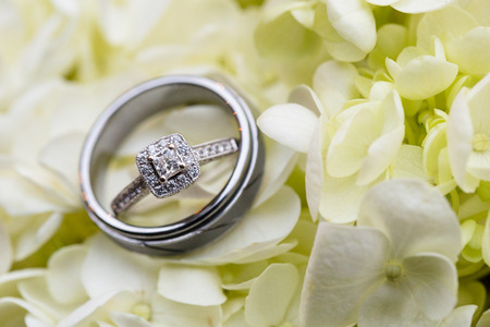 Wedding rings for the bride and groom photographed with a closeup lens on the bouquet of flowers to be carried by the bride.
