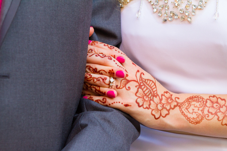 commitment committed: Bride holding onto the arm of the groom on their wedding day. The bride is wearing her wedding rings and her arms and hands are covered in henna tattoos.